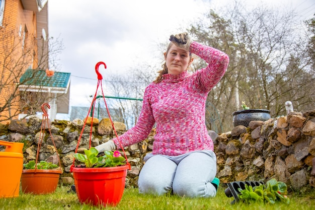 Kobieta jest zmęczona sadzeniem roślin w doniczkach zmęczona kobieta ogrodnictwem na podwórku