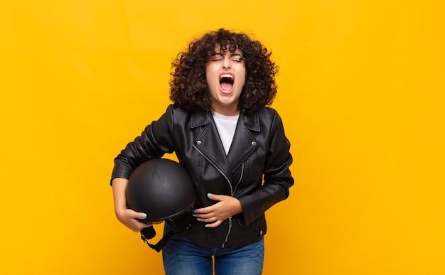 Kobieta jeżdżąca na motocyklu agresywnie krzyczy, wygląda na bardzo wściekłą, sfrustrowaną, wściekłą lub zirytowaną, krzycząc nie
