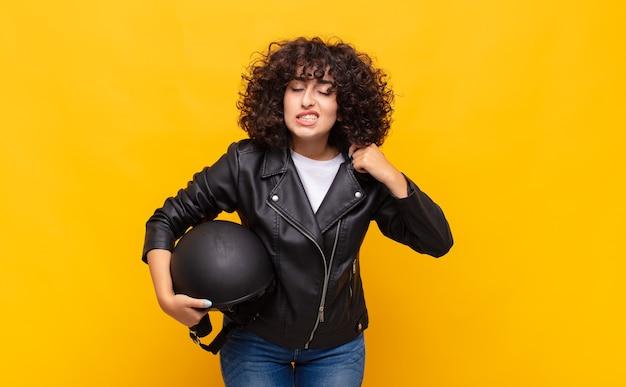 Kobieta jeżdżąca na motocyklu czuje się zestresowana, niespokojna, zmęczona i sfrustrowana, ciągnie za szyję koszuli, wygląda na sfrustrowaną problemem