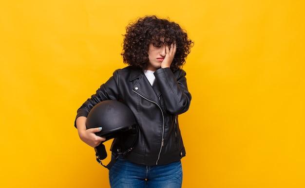 Kobieta jeżdżąca na motocyklu czuje się znudzona, sfrustrowana i senna po męczącym, nudnym i żmudnym zadaniu, trzymając twarz ręką