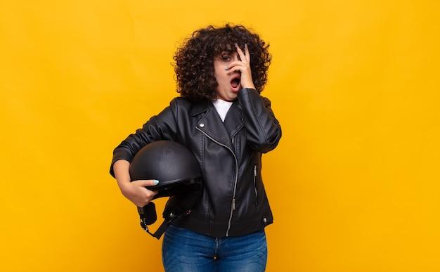 Kobieta jeżdżąca na motocyklu wyglądająca na zszokowaną, przestraszoną lub przerażoną, zakrywająca twarz dłonią i zaglądająca spomiędzy palców