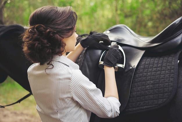 Kobieta jeźdźca cofa się i prostuje siodło na łonie natury w parku.
