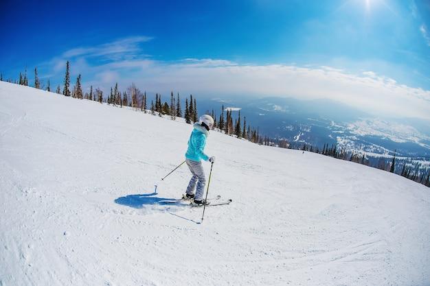 Kobieta jeździ na nartach w górach sheregesh.