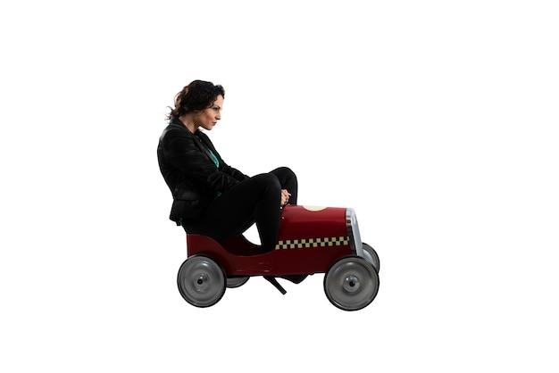 Kobieta jeździ samochodzikiem samodzielnie na białej powierzchni