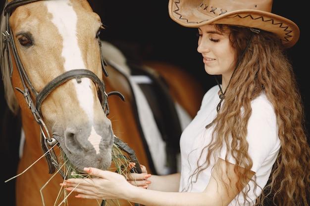 Kobieta jeździec karmi konia sianem w stajni. kobieta ma długie włosy i białą koszulkę. tło jest ciemne i czarne.