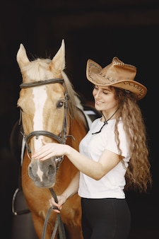 Kobieta jeździec rozmawia z koniem w stajni. kobieta ma długie włosy i białą koszulkę. tło jest ciemne i czarne.