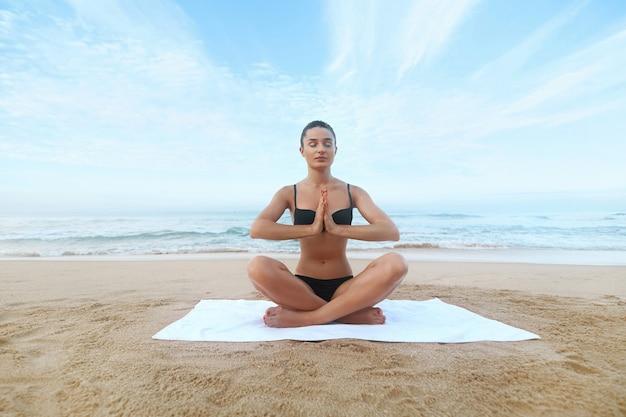 Kobieta joga plaża dla projektowania stylu życia. piękna osoba płci żeńskiej. pojęcie piękna. sport, zdrowy styl życia. poranna medytacja