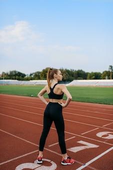 Kobieta jogger stojąc na linii startu, trening na stadionie. kobieta robi ćwiczenia rozciągające przed bieganiem na arenie na świeżym powietrzu