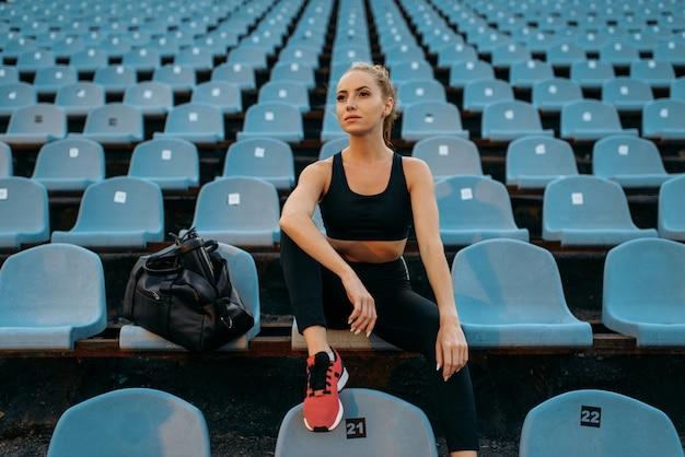 Kobieta jogger w odzieży sportowej siedzi na trybunie, trening na stadionie. kobieta robi ćwiczenia rozciągające przed bieganiem na arenie na świeżym powietrzu
