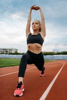 Kobieta jogger w odzieży sportowej, trening na stadionie. kobieta robi ćwiczenia rozciągające przed bieganiem na arenie na świeżym powietrzu