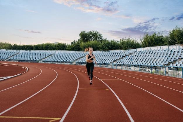 Kobieta jogger w sportowej bieganie, trening na stadionie. kobieta robi ćwiczenia rozciągające przed joggingiem na arenie na świeżym powietrzu