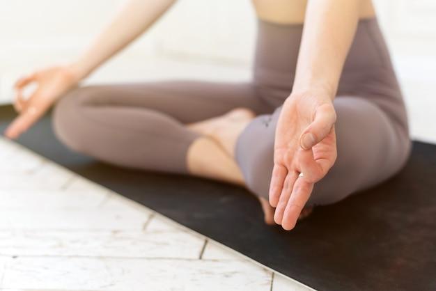 Kobieta jogi praktykujących pozę lotosu z bliska.