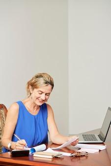 Kobieta kalkuluje jej rachunki