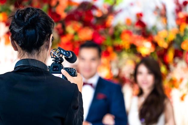 Kobieta kamerzysta z tyłu nabija się i nagrywa wideo w wydarzeniu weselnym.