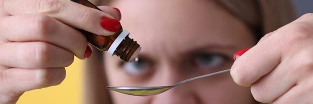 Kobieta kapie krople z bliska butelki leku. koncepcja płynnych form leków