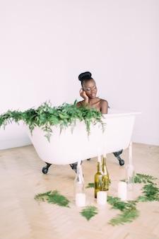 Kobieta kąpieli w wannie pełnej piany. piękna amerykanin afrykańskiego pochodzenia panna młoda w dekorującej skąpaniu
