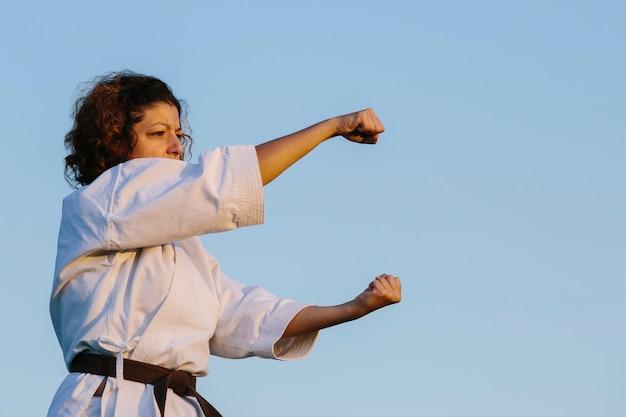 Kobieta karate, uderzająca pięścią, ubrana w kimono. koncepcja karate i sztuk walki