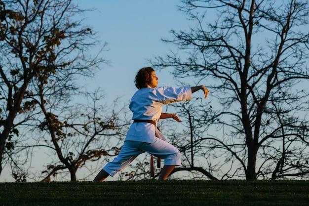 Kobieta karate w postawie obronnej, ubrana w kimono. koncepcja karate i sztuk walki