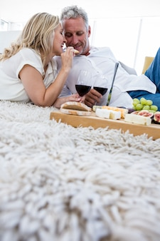 Kobieta karmi jedzenie mężczyzna podczas gdy kłamający na dywaniku
