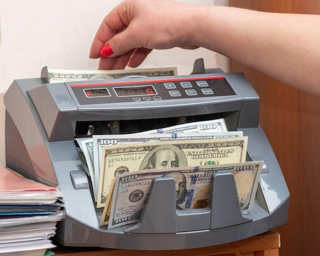 Kobieta kasjerka wkłada sto dolarów amerykańskich banknotów do kasy przy kasie