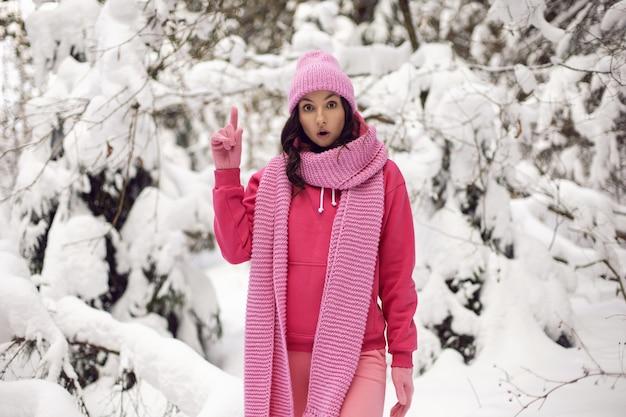 Kobieta kciuki w górę pomysł ciesz się w różowych ubraniach kurtka, szalik z dzianiny i czapka stoi zimą w zaśnieżonym lesie