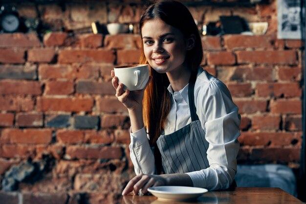 Kobieta kelner filiżanka kawy siedzi przy stole zabawa praca
