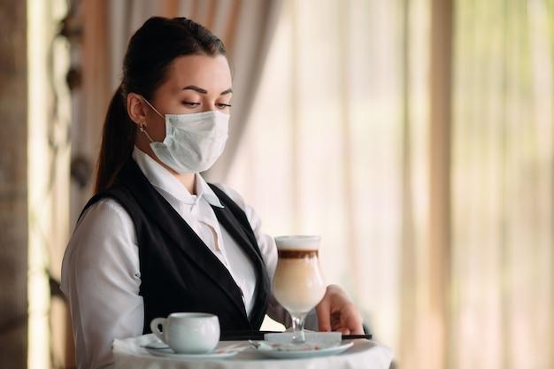 Kobieta kelner o europejskim wyglądzie w masce medycznej podaje kawę latte.