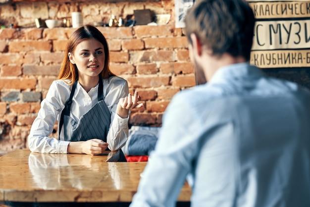 Kobieta kelner przynosi kawę klientowi kawiarni obsługi
