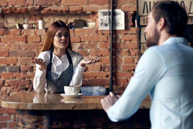 Kobieta kelner przynosi kawę klientowi kawiarni