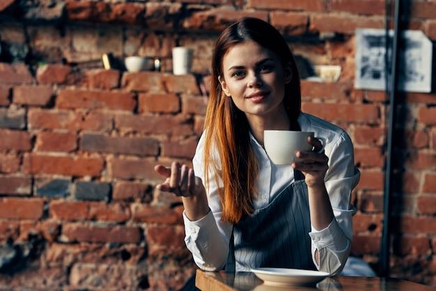Kobieta kelner w zamawianiu usługi filiżanki kawy fartuch