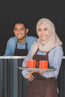 Kobieta kelnerka serwująca kawę w kawiarni