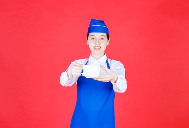 Kobieta kelnerka w mundurze stojąc i trzymając kubek na czerwonej ścianie.