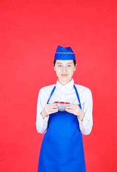 Kobieta kelnerka w mundurze stojąc i trzymając miskę na czerwonej ścianie.