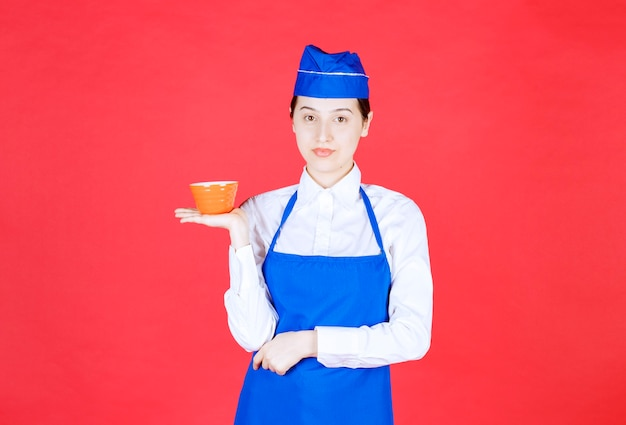 Kobieta kelnerka w mundurze stojąc i trzymając pomarańczową miskę.