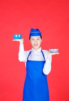 Kobieta kelnerka w mundurze stojąca i trzymająca kolorowe miski na czerwonej ścianie.