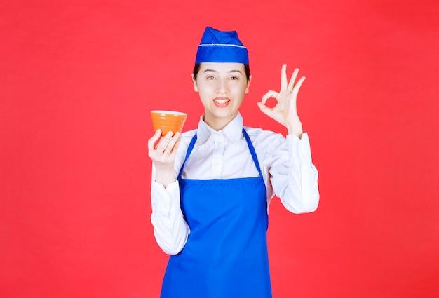 Kobieta kelnerka w mundurze trzyma pomarańczową miskę i pokazuje ok gest.
