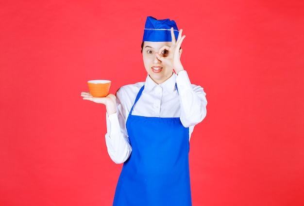 Kobieta kelnerka w mundurze trzyma pomarańczową miskę i robi ok gest w pobliżu oka.