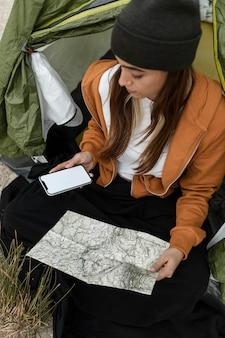 Kobieta, kemping i patrząc na mapę wysoki widok
