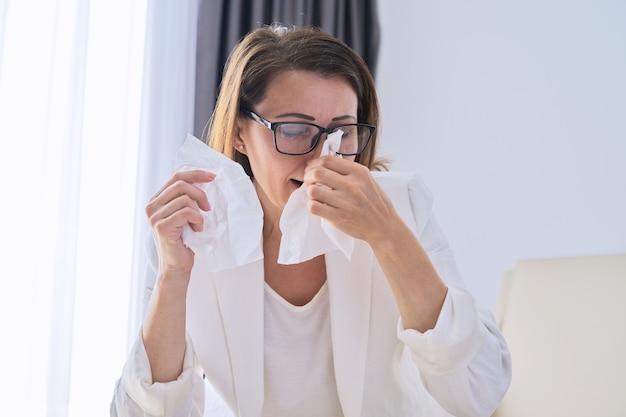 Kobieta kicha w chusteczce, bizneswoman zachorowała w biurze, z objawami choroby układu oddechowego. sezonowe przeziębienia, alergia sezonowa, sezon grypowy, pandemia