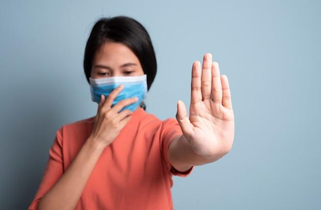 Kobieta kichanie i obejmujące usta i nos podczas kaszlu grypy.