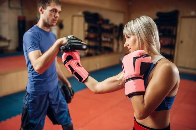 Kobieta kickboxer ćwiczy uderzenie ręką