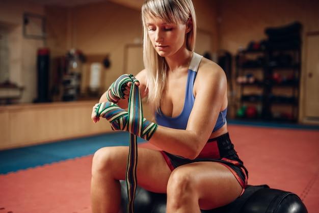 Kobieta kickboxer siedzi na worek treningowy w siłowni