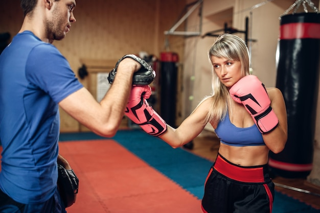 Kobieta kickboxer w rękawiczkach ćwiczy uderzenie ręką z męskim trenerem osobistym w ochraniacze, trening na siłowni. kobieta bokser na treningu, praktyka kickboxingu