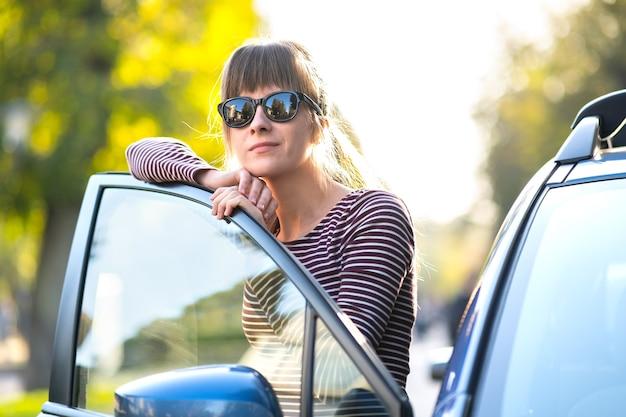 Kobieta kierowca ciesząc się ciepły letni dzień stojąc obok swojego samochodu na ulicy miasta
