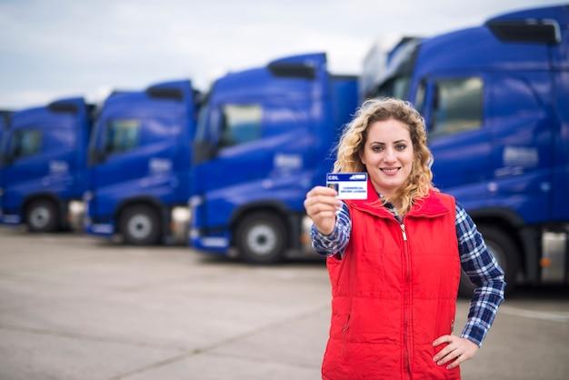 Kobieta kierowca ciężarówki dumnie trzyma komercyjne prawo jazdy.