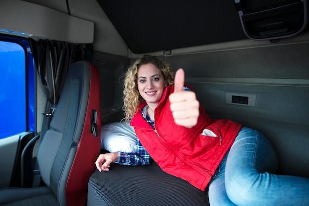 Kobieta kierowca ciężarówki, leżąc na łóżku kabiny pojazdu, pokazując kciuk do góry