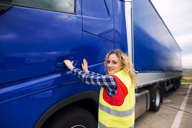 Kobieta kierowca ciężarówki, otwierając drzwi kabiny i wchodząc do pojazdu ciężarowego