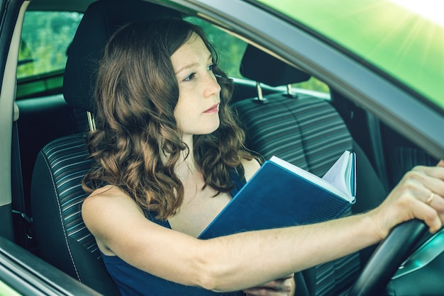 Kobieta kierowca czytając książkę w samochodzie