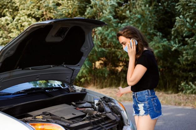 Kobieta kierowca dzwoni do biura naprawy samochodów i opisuje problem z samochodem