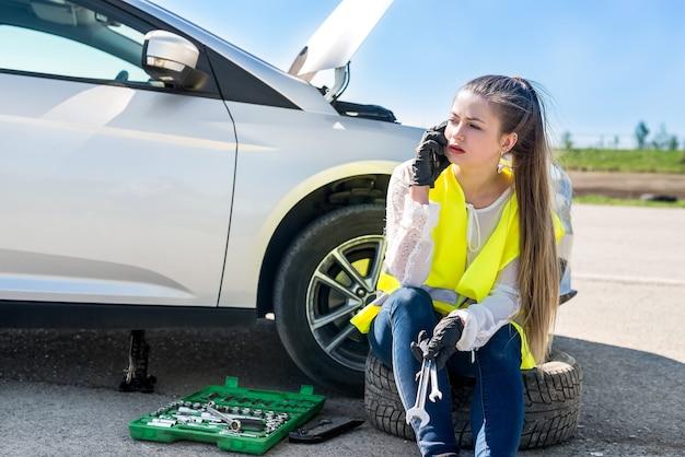 Kobieta kierowca dzwoniąc, prosząc o pomoc w serwisie samochodowym